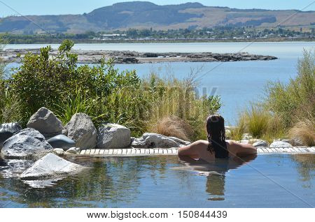 Young woman having a spa in outdoors hot pool in Rotorua New Zealand.