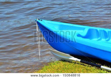 Blue Kayak On River Bank
