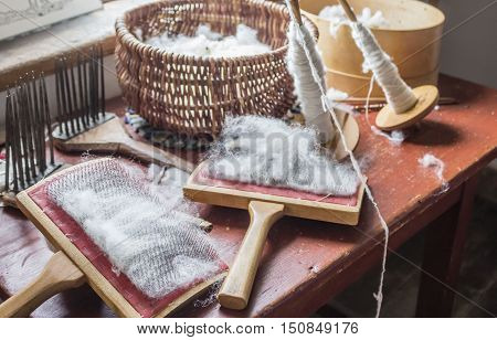 horizontal image of wool carding brushes with wool  in a basket lying on a table