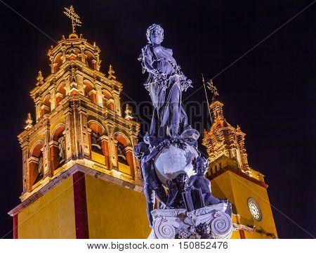 Our Lady of Guanajuato Paz Peace Statu Night Guanajuato Mexico Statue donated To City by Charles V Holy Roman Emperor in the 1500s. Steeple Towers Basilica de Nusetra Senora Guanajuato Mexico