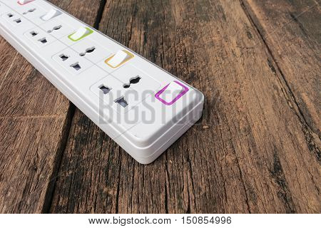 white plug socket electric power bar or extension block Select focus with shallow depth of fieldon wooden table background and copy space