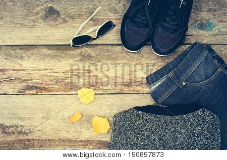Women's clothing and accessories: grey sweater, jeans, sneakers, sunglasses and yellow leaves on wooden background. Top view. Toned image.