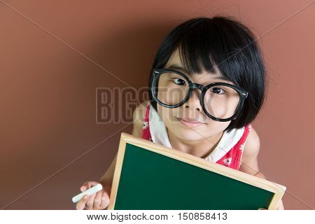 Asian school child with blank green chalkboard and chalk for education conceptual