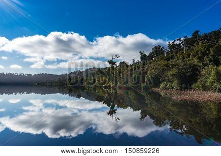 Lake Ianthe on calm sunny day landscape. Perfect water reflection of water edge with sun rays and sun flare. South Island New Zealand