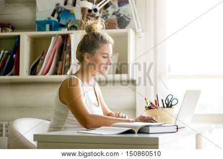 Side view portrait of beautiful young smiling woman working or studying using laptop at small home office or in the student dorm. Indoors image