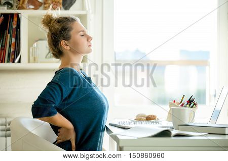 Portrait of an attractive woman in a chair at the table with cup and laptop, book, pencils, notebook on it. Concept photo