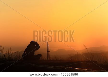 Silhouette of traveler when he is taking photograph on mountain at sunrise.
