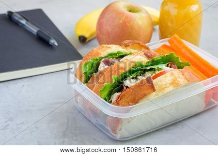 Lunch box with chicken salad sandwiches served with carrot sticks. Fruits and juice on background horizontal copy space