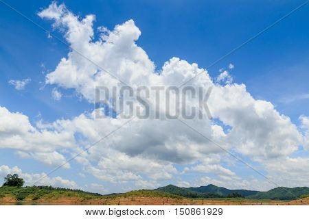 Blue sky with white clouds and hill