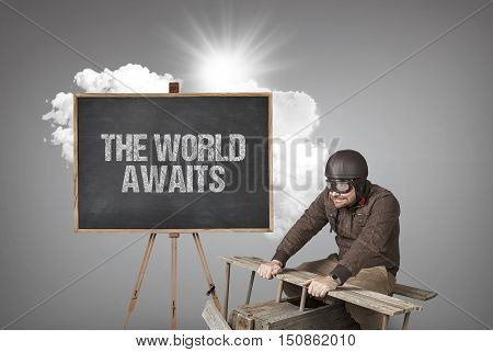 The world awaits text on blackboard with businessman and wooden aeroplane