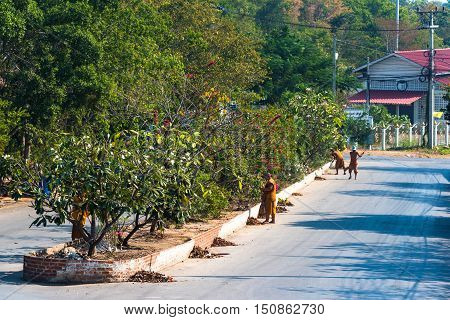 Hua Hin Thailand - Dec 28 2015: Buddhist monks at cleaning work on early morning sweeping streets near Wat Etisukatow temple