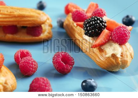 Delicious eclairs and berries on blue background