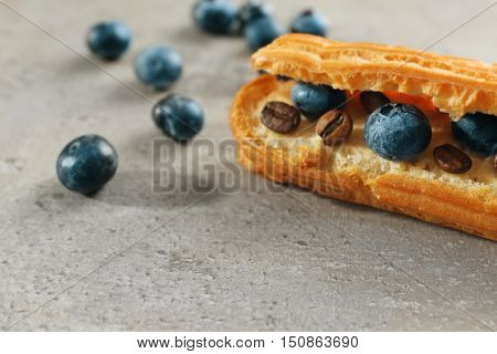 Delicious eclair with berries and coffee grains on light textured background