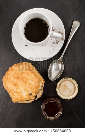 sweet british raisin scone and a glass filled with honey cup hot instant coffee also small spoon on slate