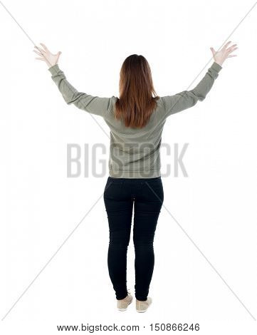 Back view of Beautiful woman looking at wall and Holds  hand up. young girl standing. Rear view people. Isolated over white background. A woman in a gray sweater raised his hands to the sky