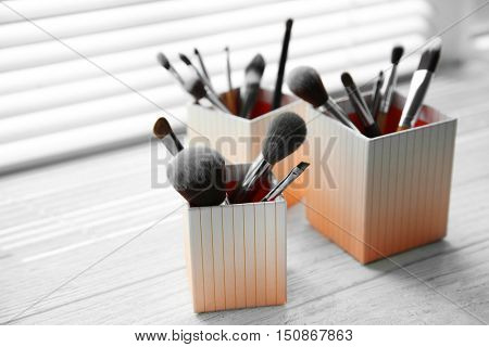Set of makeup brushes in decorative boxes on windowsill