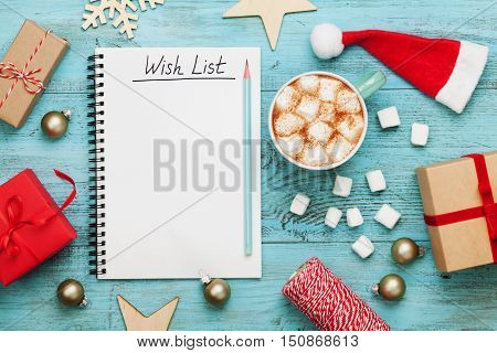 Cup of hot cocoa or chocolate with marshmallow holiday decorations and notebook with wish list on turquoise vintage table from above, christmas planning concept. Flat lay style.