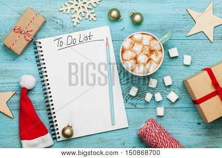 Cup of hot cocoa or chocolate with marshmallow holiday decorations and notebook with to do list on turquoise vintage table from above, christmas planning concept. Flat lay style.