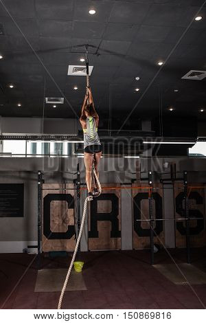 Fitness woman rope climb cxercise In gym.