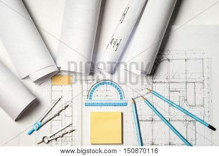 Workplace of architect - Architect rolls and plans.architectural plantechnical project drawing. Engineering tools view from the top. Construction background.
