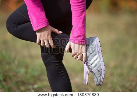 Warming up outdoors in the autumn, holding an ankle, stretching after or before running. Concept photo