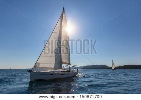 Sailboat at the finish regatta race in the backlight.
