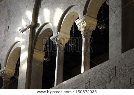 Colonnade with iron chandeliers in a Romanesque church