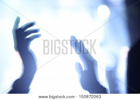 Hands clapping in backlight during a live show