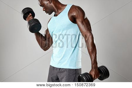 Fit Young Black Man Exercising With Dumbbells