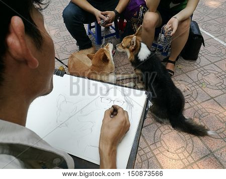 Asian portrait painter drawing sketch portrait of a couples with their dogs by pencil