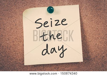 seize the day. note message on a bulletin board