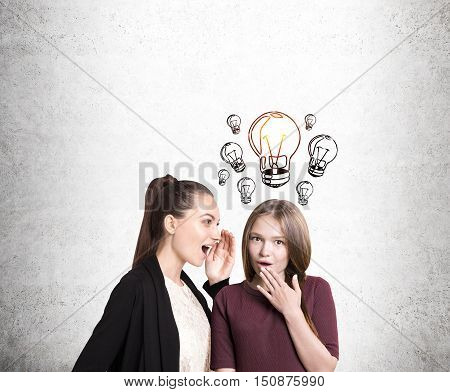 Portrait of two girlfriends gossiping. One of them is surprised and has an idea. Concept of intrigues and plot twists in our lives