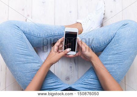 Top view of woman wearing blue skinny jeans and white sneakers and holding a smartphone. Concept of teenage life and gadgets