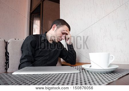 portrait of exhausted worker in black shirt sleeping on his desktop in cafe with cup of coffee
