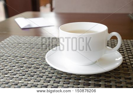 Standing on the table white Cup of tea and a white letter with the receipt for payment