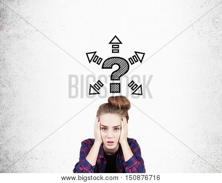 Stressed girl in checkered shirt is holding her hand in both hands and looking at the viewer. Question mark sketch and arrows are around it. Concept of decision making