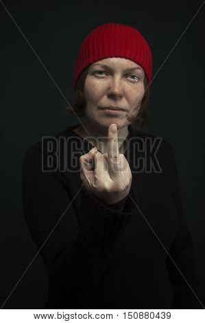 Aggressive punk woman with red cap showing middle finger low key image. Selective focus on middle finger.