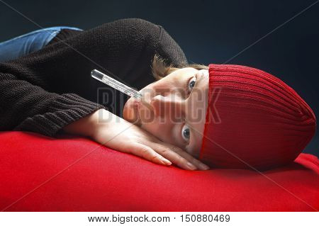 A young girl holding thermometer with lips. Healthcare and medicine concept.