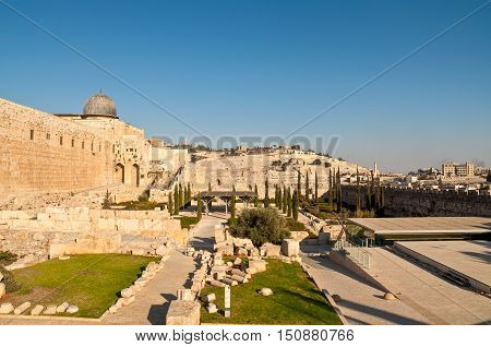View of the Mount of Olives from the Temple Mount. A portion of the wall around the old city of Jerusalem is visible in the center with the two arches. On the hillside of the Mount of Olives is the Jewish cemetery.