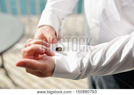 Groom fixing cufflinks of white shirt in wedding day