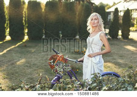 Woman with a bicycle walks through the park on a sunny day.