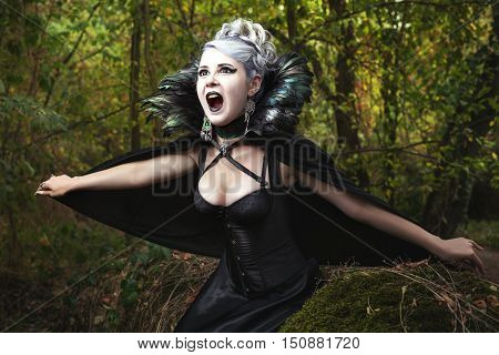Scary girl screams she in gothic black dress in the forest.