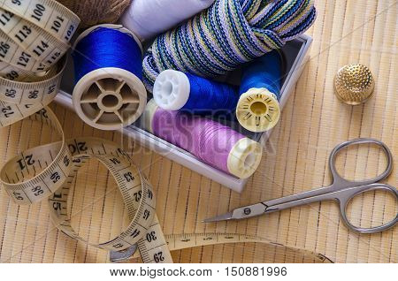 Wood background with sewing. Scissors centimeter bobbins with thread and needles .