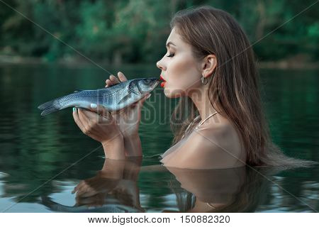 Girl standing in the water in her hands trout fish she talks to her.