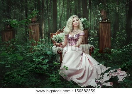 Girl in evening dress sits on a an armchair in the fairy forest.