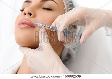 Close up of surgeon arms making botox injection into female face. Serene young woman is lying and relaxing