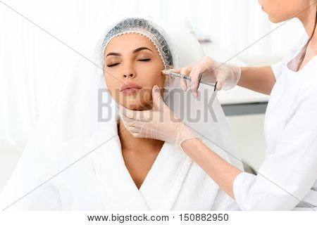 Relaxed young woman is getting botox injection at clinic. She is sitting and closed eyes. Doctor is standing and touching syringe needle to her cheek