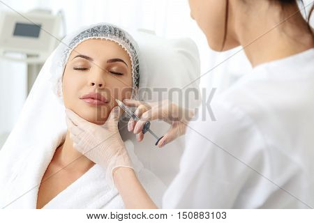 Young woman is getting botox procedure with enjoyment. Skillful surgeon is injecting liquid into her cheek