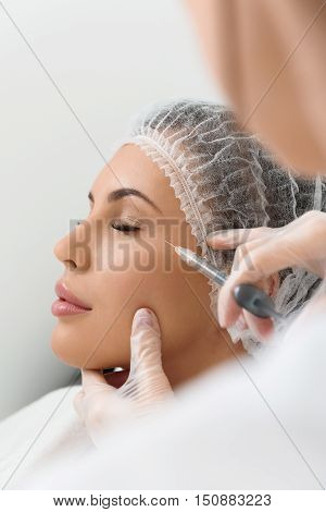 Professional beautician is injecting botox into female eye area. Young girl closed eyes with relaxation