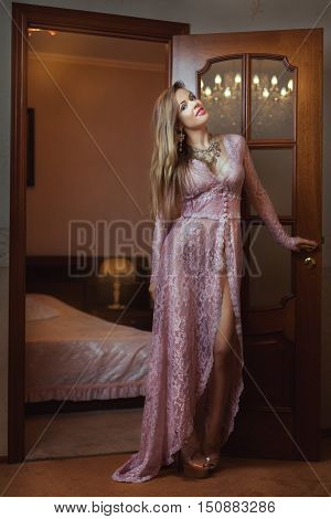 Girl in peignoir standing near the door to the bedroom.